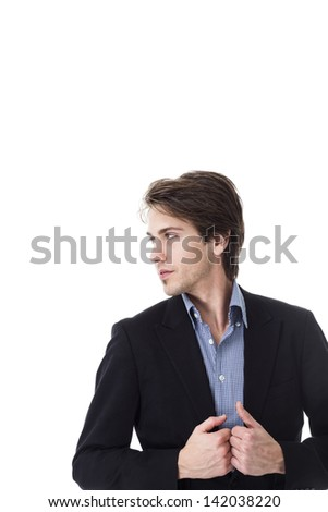 Dark studio portrait of a serious man standing in the shadows with his arms folded and a pensive expression - stock photo