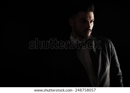 Dark studio shot of a young business man looking away from the camera.