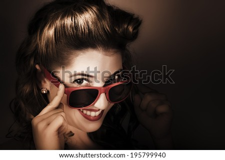 Dark summer portrait on the face of an attractive young pin up woman wearing sunglasses, diamond earrings, classic styled makeup and fifties hairdo. Retro cool - stock photo