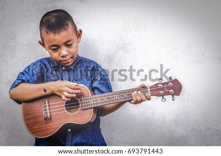 Dark tone Asian boy Black birthmarks on hand Wearing shirt fashion Jeans Play ukulele cool gesture Passionate love music empty space Old cement wall Child Development Concept Grandson name Promphum
