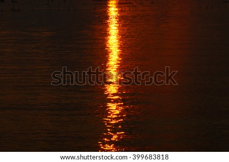 Dark tone colorful sunrise reflection lighting water on lake in the morning:select focus with shallow depth of field:ideal use for background. - stock photo