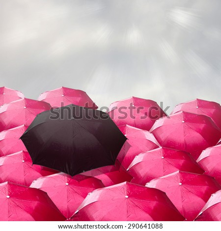 dark umbrella over many red ones.The concept of bad leadership. - stock photo