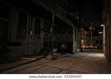 Dark urban city alley at night with loading dock and cars.