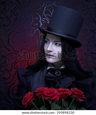 Dark Valentine. Romantic portrait of young woman in gothic man image posing with red roses - stock photo