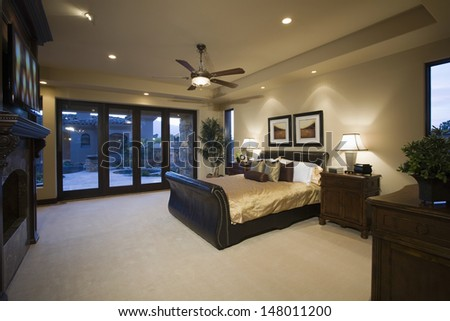 Dark wood furniture in bedroom with ceiling fan - stock photo