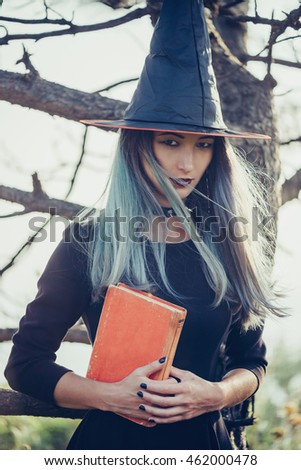 Dark young witch standing with book in the forest, looking at camera. Space for text on book