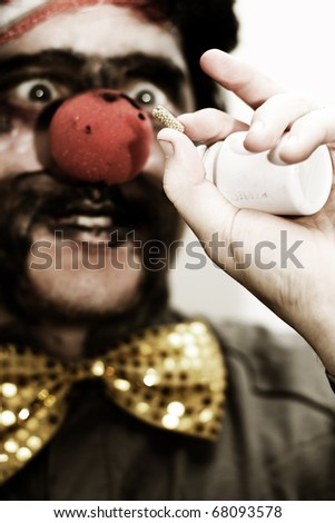 Darkened Image Of A Clown Holding Up A Prescribed Medication Tablet To Help Bring His Humor Back - stock photo