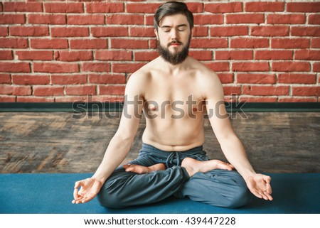 Darkhaired man with closed eyes, dark hair and beard wearing trousers doing yoga position and sitting on blue matt at wall background, position of fingers in mudra, copy space, portrait. - stock photo