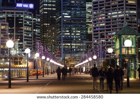 DARLING HARBOUR, AUSTRALIA - JUNE 4, 2015; Pedestrians walking across The Pyrmont Bridge, a swing bridge across Cockle Bay, Darling Harbour, towards Sydney and the CBD buildings and offices. - stock photo