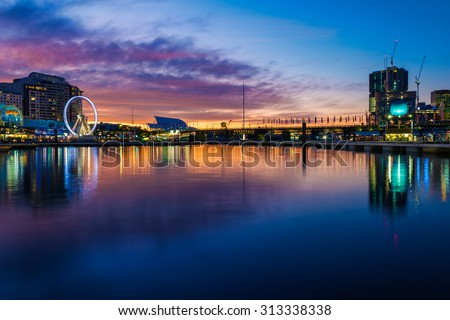 Darling Harbour in Sydney on a winters evening, with the highrise buildings being built, and the casino and amusement park on the left bank - stock photo