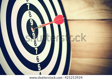 Dart arrow hitting in the target center of dartboard - stock photo