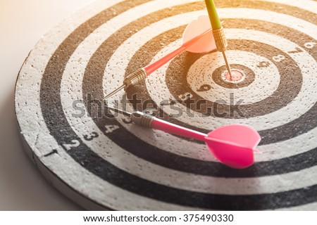 dart arrow hitting in the target center of dartboard,abstract of success