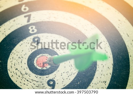 dart arrow hitting in the target center of dartboard,abstract of success - stock photo