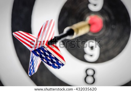 Dart arrow with usa flag  hitting in the target center of dartboard,shallow DOF - stock photo