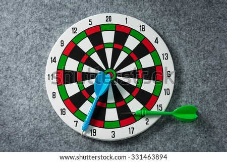 Dart board with a green arrow and blue placed on the gray carpet. Failure of thought and success hitting target aim goal achievement concept background. - stock photo