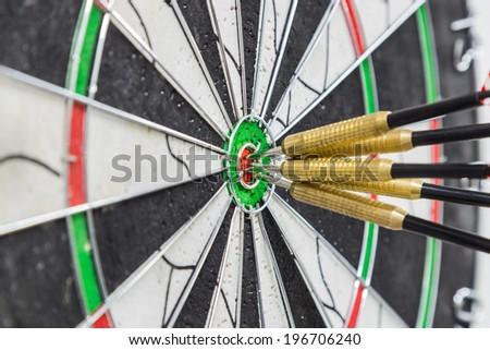 Dart board with darts on bullseye - stock photo