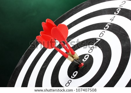 dart board with darts on green background - stock photo