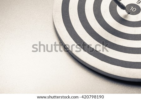 Dart hit the center of dartboard in abstract composition for copy space - stock photo