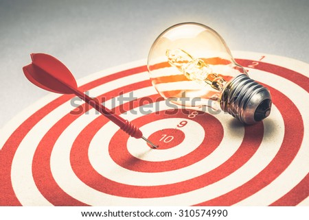 Dart hit the center of dartboard with glowing light bulb, - stock photo