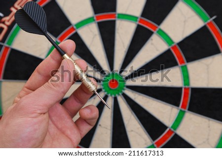 dart in a hand and a dartboard