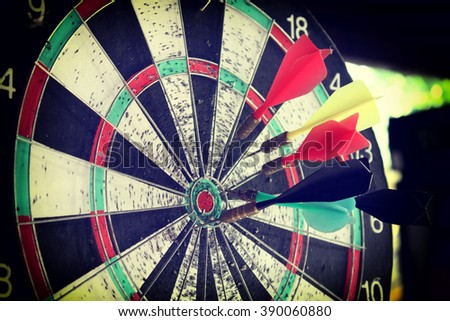 Dart in bulls eye of dartboard concept for hitting target - stock photo