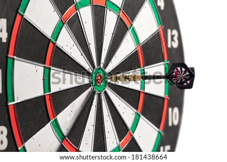 Dart in the center of a dart board scoring a bulls eye conceptual of winning, accuracy, skill, challenge and achievement, isolated on white - stock photo