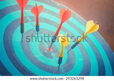 Dart is an opportunity and Dartboard is the target and goa with vintage retro picture stylel. success/fail business concept. Bullseye and Dart. - stock photo