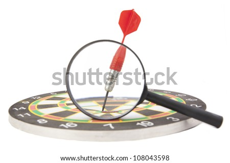 dart stuck in the target increases through a magnifying glass - the idea of examining the exact result - stock photo