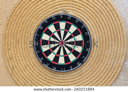 Dartboard against rope background - stock photo