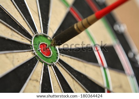 Dartboard with dart on bullseye