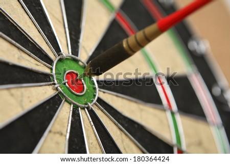 Dartboard with dart on bullseye - stock photo