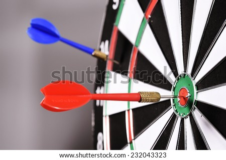 Dartboard with darts on gray background.