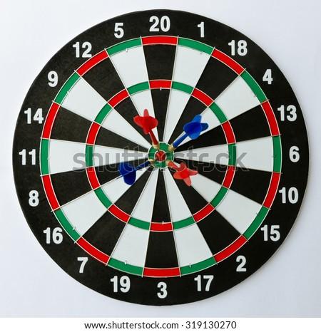 Dartboard with four darts on the bulls eye. - stock photo