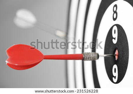 Dartboard with red darts on gray background. - stock photo