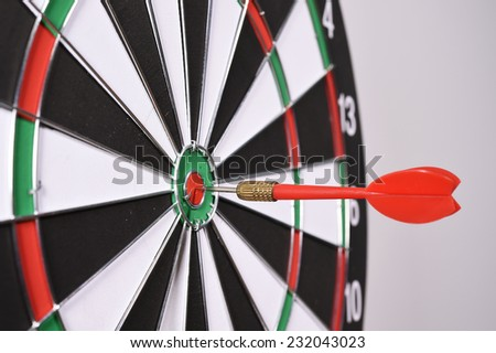 Dartboard with red darts on gray background.
