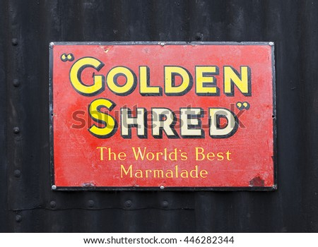 DARTMOOR, DEVON, UK - MARCH 27 2015: Vintage Golden Shred metal advertising plaque fixed to black corrugated iron wall