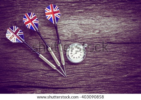 Darts and watch on old wooden background. Vintage style. - stock photo