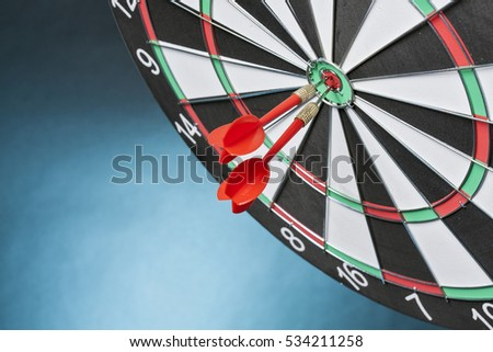 Darts arrows hitting the target center on a light blue background