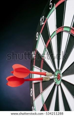 Darts arrows hitting the target center on a purple background