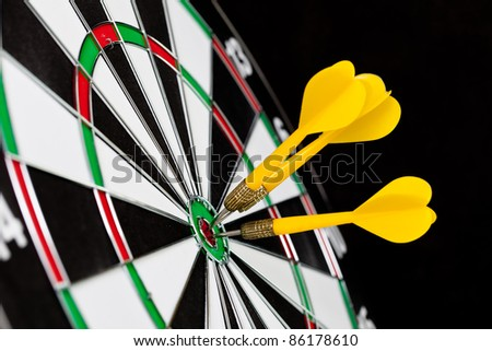 Darts hitting the bullseye on a dartboard - stock photo