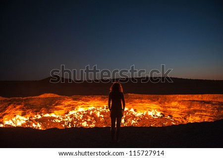 Darvaza, Turkmenistan - Staring into the flaming gas crater known as the Door to Hell In Darvaza, Turkmenistan. - stock photo