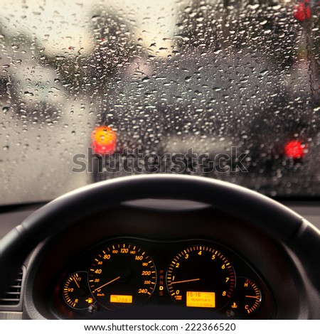 dashboard and rain droplets on car windshield - stock photo