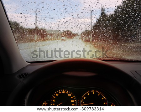 dashboard and rain droplets on car windshield