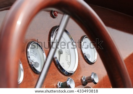 Dashboard and steering wheel of a classic wooden speedboat.