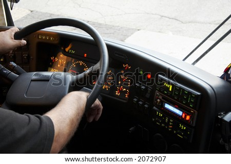 dashboard of a bus with the arms of the bus driver