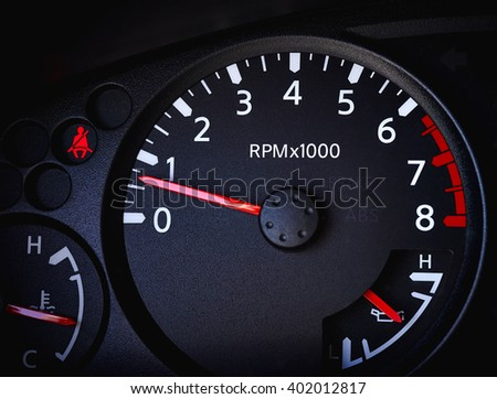 Dashboard of a car showing tachometer, partial speedometer, temperature gauge, battery guage, seat belt warning light and open door warning light