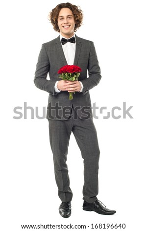 Dashing groom in a tuxedo holding a bunch of red roses - stock photo
