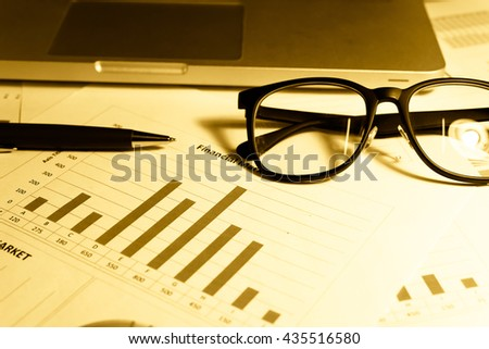 Data analyzing in trading market with pen. Working set for analyzing financial statistics and analyzing a market data. Data analyzing from charts and graph to find out the result. - Vintage tone.