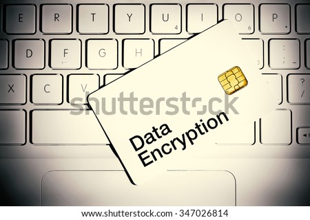 Data Encryption concept. Smart card on a keyboard of white laptop computer.
