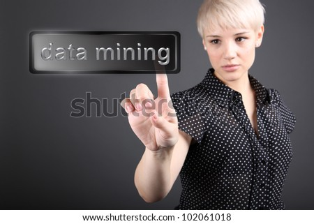 Data mining concept - business woman touching screen - stock photo